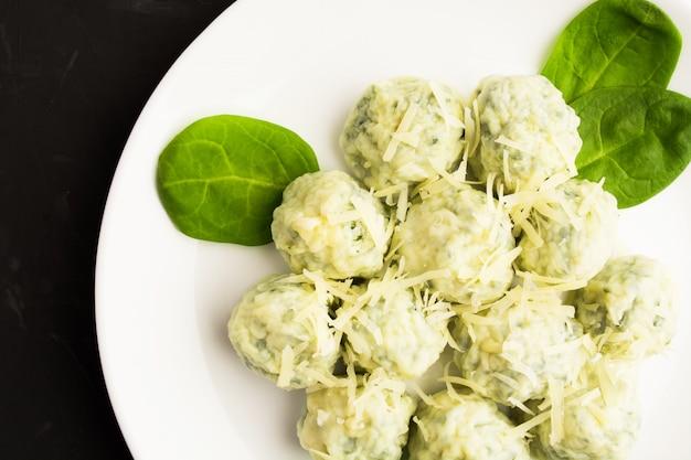 Gnocchi degli spinaci del formaggio sul piatto bianco