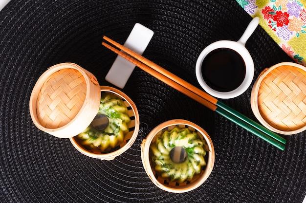 Gnocchi di erba cipollina di aglio cotto a vapore dim sum casalingo concetto asiatico dell'alimento in canestro di bambù di dim sum