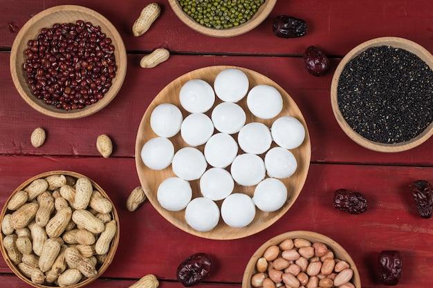 Gnocchi dolci nella ciotola sul tavolo, ang pow o pacchetto rosso e lingotti d'oro