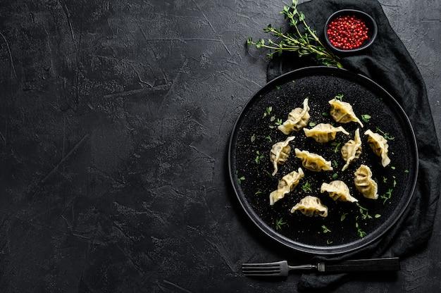 Gnocchi fatti in casa ripieni di carne. sfondo nero. vista dall'alto.