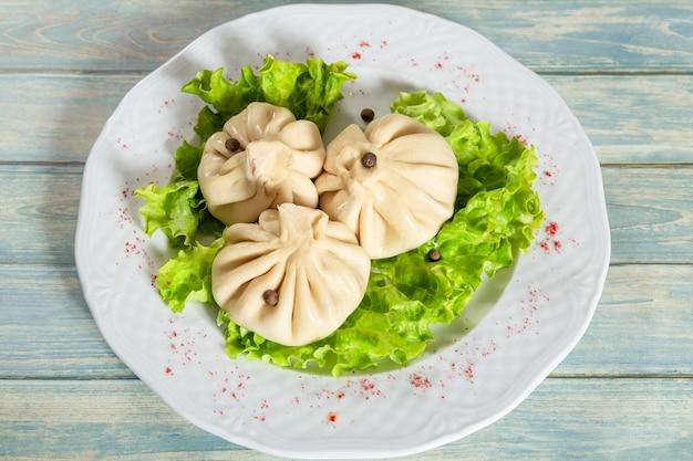 Gnocchi georgiani khinkali con carne, lattuga e pepe sul piatto bianco sulla tavola di legno