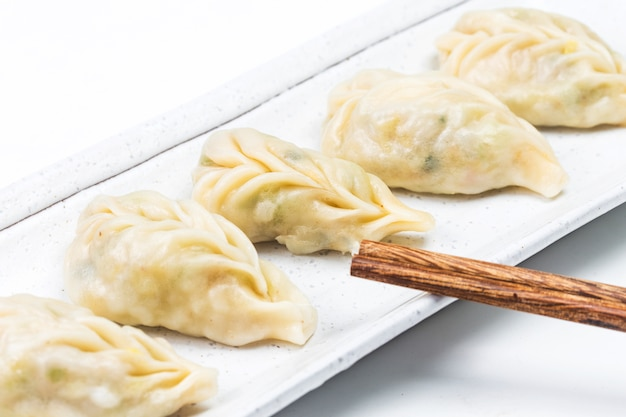 Gnocco bollito fresco sul piatto. cibo cinese con vapori caldi su sfondo.