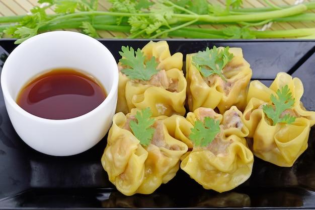 Gnocco cotto a vapore cinese del gamberetto con salsa sul piatto