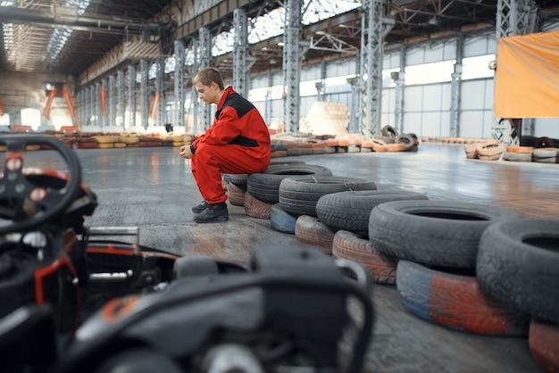 Go kart racer seduto su pneumatici, karting sport auto