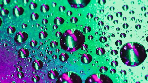 Gocce d'acqua fresca sullo sfondo riflettente verde e viola