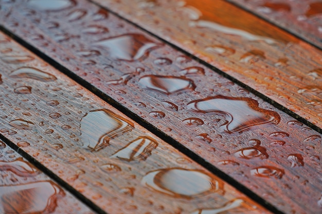 Gocce d'acqua su una superficie del pavimento in legno. goccia d'acqua su legno con goccia di pioggia dopo una pioggia.
