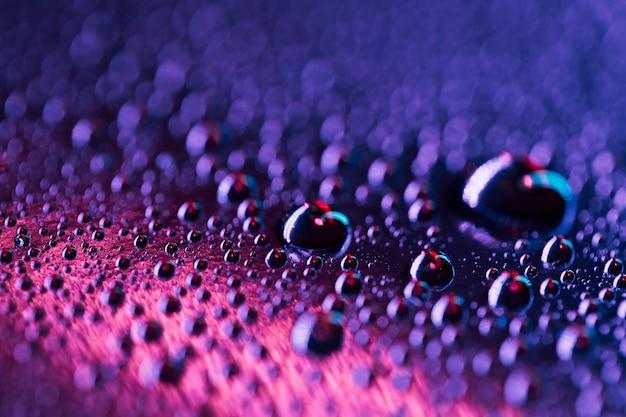 Gocce d'acqua su una superficie di vetro brillante blu e rosa