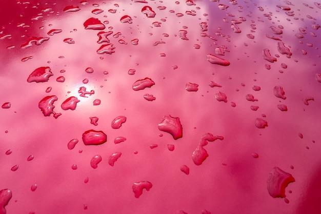 Gocce d'acqua su una superficie rosa brillante.