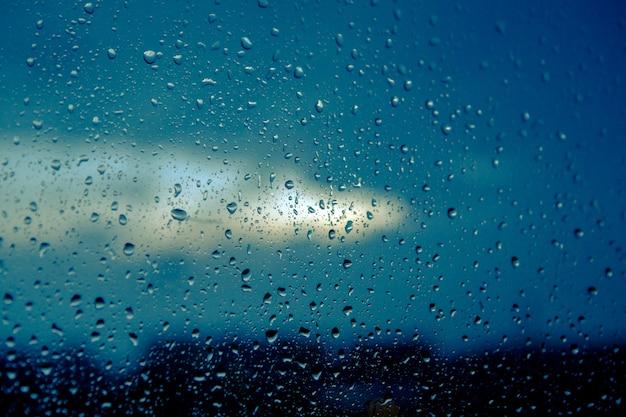 Gocce d'acqua su vetro contro il cielo nuvoloso blu la sera