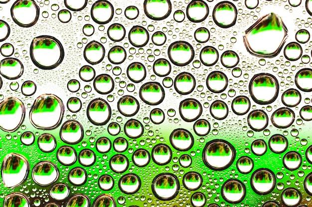 Gocce d'acqua su vetro trasparente verde
