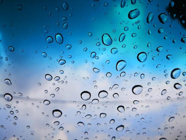 Gocce d'acqua sullo specchio di vetro con nuvole e sfondo sfocato cielo blu