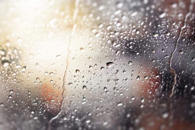 Gocce d'acqua vista attraverso il parabrezza di una forte giornata di pioggia, composizione di profondità di campo.