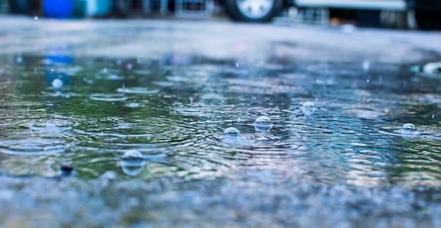 Gocce dell'acqua piovana e sul fondo della sfuocatura dell'estratto della strada