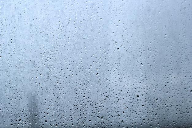 Gocce della pioggia su un fondo di vetro dell'estratto di struttura