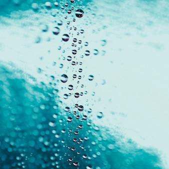 Gocce di acqua astratte su sfondo di vetro turchese