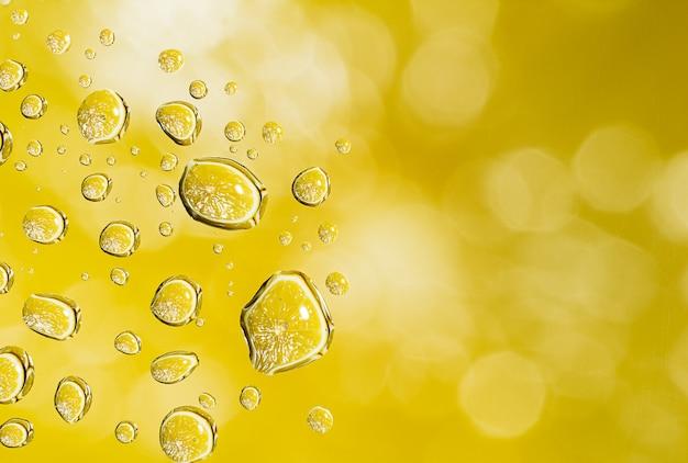 Gocce di acqua gialle astratte sulla superficie del vetro