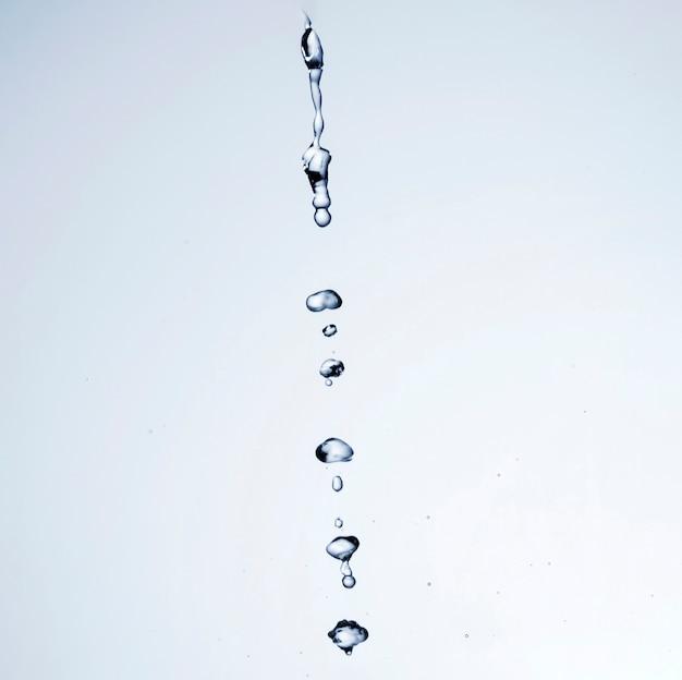 Gocce di liquido trasparente su sfondo bianco con spazio di copia