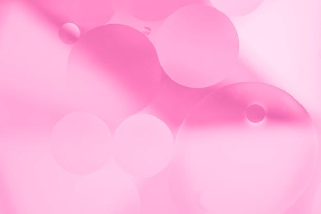 Gocce di olio rosa sulla superficie dell'acqua