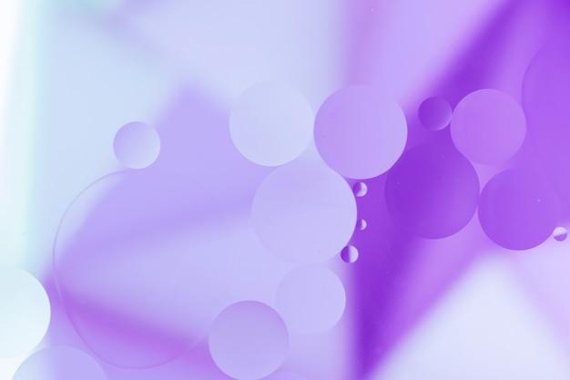 Gocce di olio viola sulla superficie di colore pallido