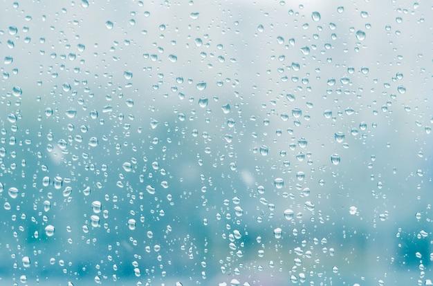 Gocce di pioggia e acqua congelata sul fondo del vetro di finestra, tonalità blu