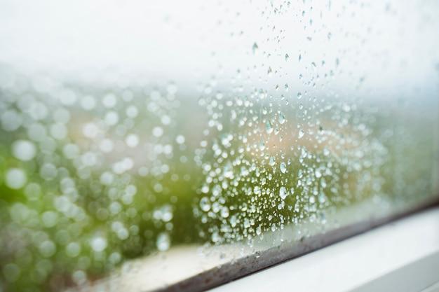 Gocce di pioggia sfondo orizzontale. stagione invernale. umidità e tempo piovoso all'interno della casa. condensa dell'acqua sulla finestra. il dettaglio delle gocce bagnate di pioggia attacca ad una finestra pulita a casa.