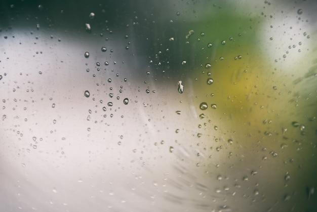 Gocce di pioggia su vetro vetro della finestra di giorno di pioggia con gocce d'acqua e sfondo verde sfocatura natura
