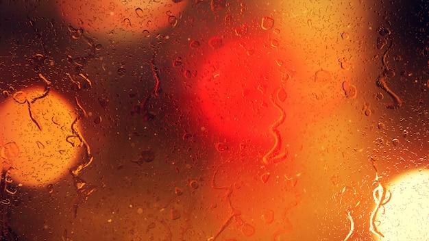 Gocce di pioggia sul finestrino di una macchina con meravigliosamente sfocato sfondo di semafori di strada