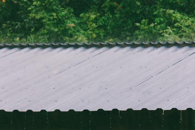 Gocce di pioggia sul tetto di metallo in una giornata estiva