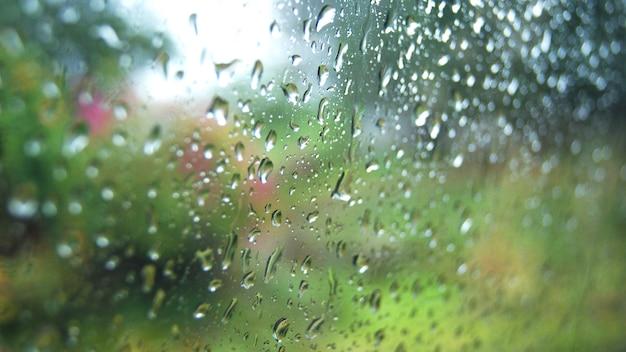 Gocce di pioggia sul vetro vetro della finestra di giorno piovoso con gocce di pioggia