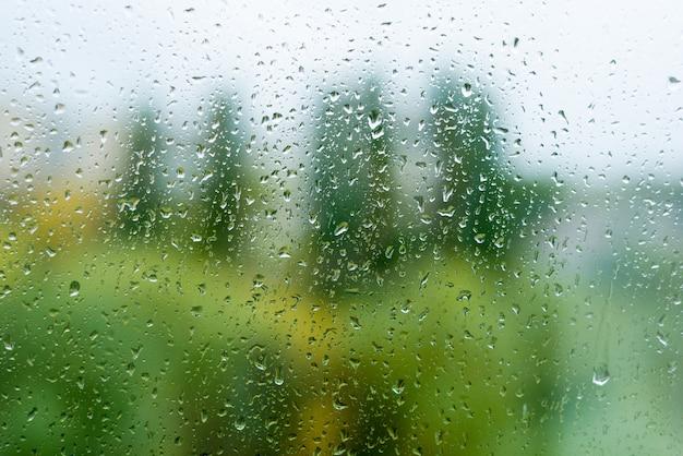 Gocce di pioggia sulla finestra di autunno, fondo urbano