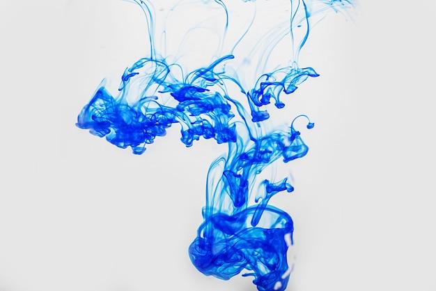 Gocce di vernice blu astratte in acqua