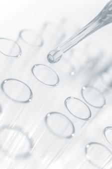 Gocce liquido chimico nella provetta nel colpo alto vicino del laboratorio