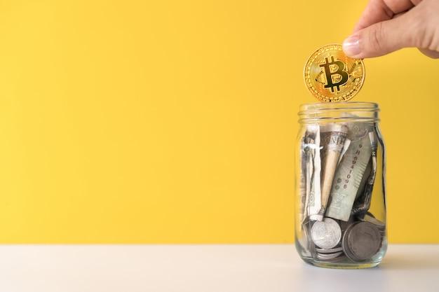 Goccia a mano bitcoin d'oro il barattolo pieno di monete e banconote che significa risparmio sugli investimenti con la rete online di criptovaluta denaro digitale fintech.