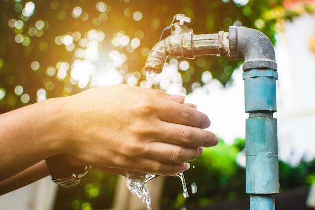 Goccia d'acqua dal rubinetto su sfondo verde