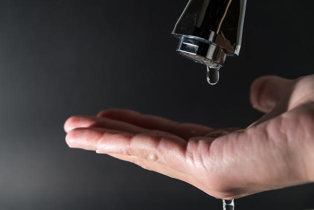 Goccia d'acqua sul rubinetto con sfondo nero