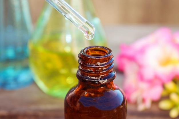 Goccia d'olio che gocciola dalla pipetta in bottiglie di olio essenziale