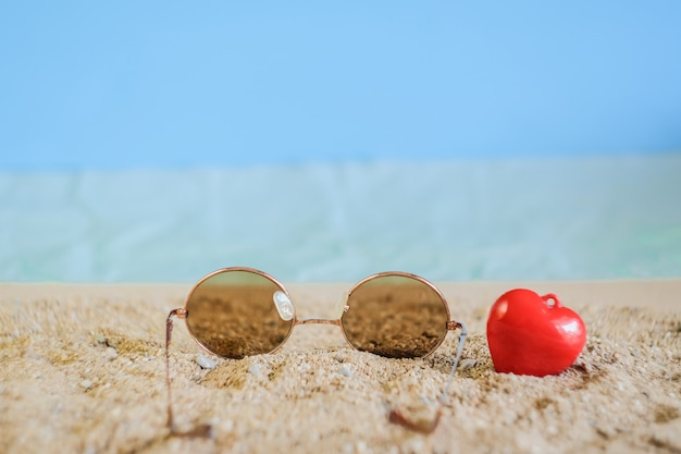Goccia del eyeware degli occhiali da sole sulla spiaggia di sabbia tropicale.