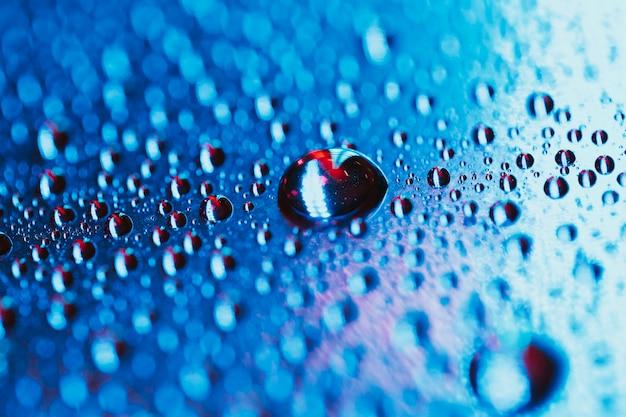 Goccia dell'acqua sui precedenti blu luminosi del bokeh