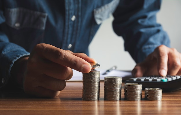 Goccia della mano una moneta con la pila di monete dei soldi in crescita per il business. concetto finanziario e contabile.