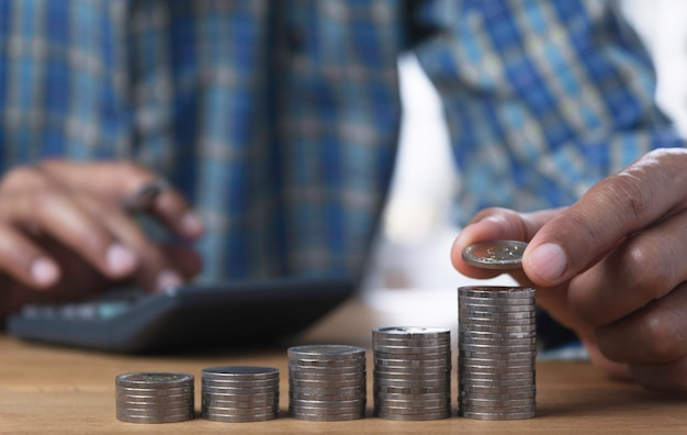 Goccia della mano una moneta con la pila di monete dei soldi in crescita per il business