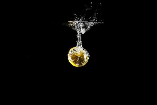 Goccia di limone in acqua nera