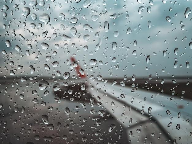 Goccia di pioggia alla finestra dell'aeroplano prima del decollo durante la stagione dei monsoni.