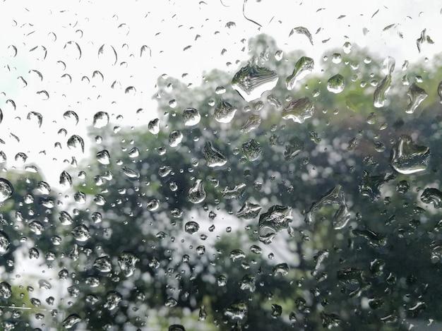 Goccia di pioggia che cade sull'automobile di vetro della finestra.
