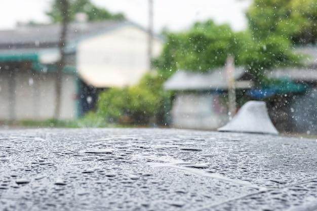 Goccia di pioggia del primo piano che cade sull'automobile del tetto