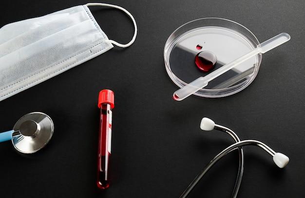 Goccia di sangue in una capsula di petri di vetro, provetta con campione medico, mascherina medica e stetoscopio