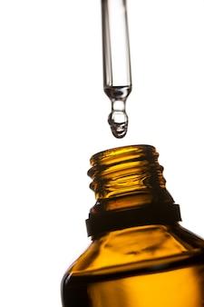 Goccia di stillicidio olio dalla pipetta nella bottiglia di olio essenziale