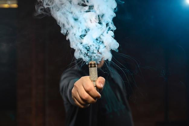 Gocciolatore in una mano facendo una nuvola di fumo