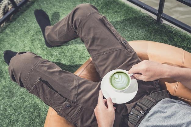 Godendo il caffè fresco. equipaggi i pantaloni da portare d'uso e la tazza della tenuta mentre si rilassano sullo strato a casa