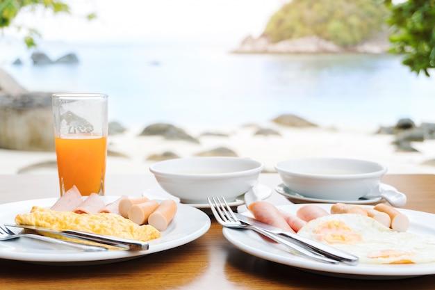 Godendo la colazione vicino al concetto di estate mare tropicale