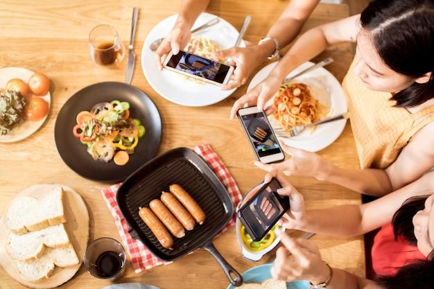 Goditi la cena mangiando la festa con gli amici e scattando foto per telefono per postare nella rete sociale